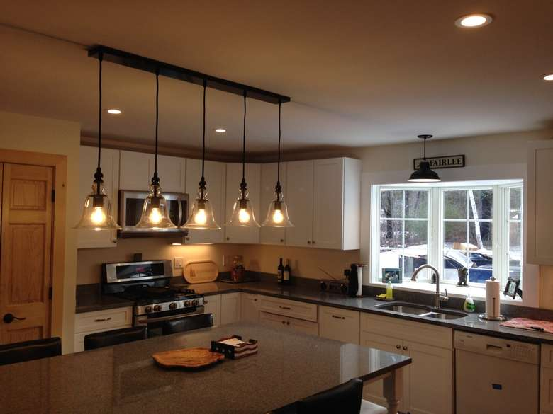 newly remodeled kitchen with a large island and pendant lights