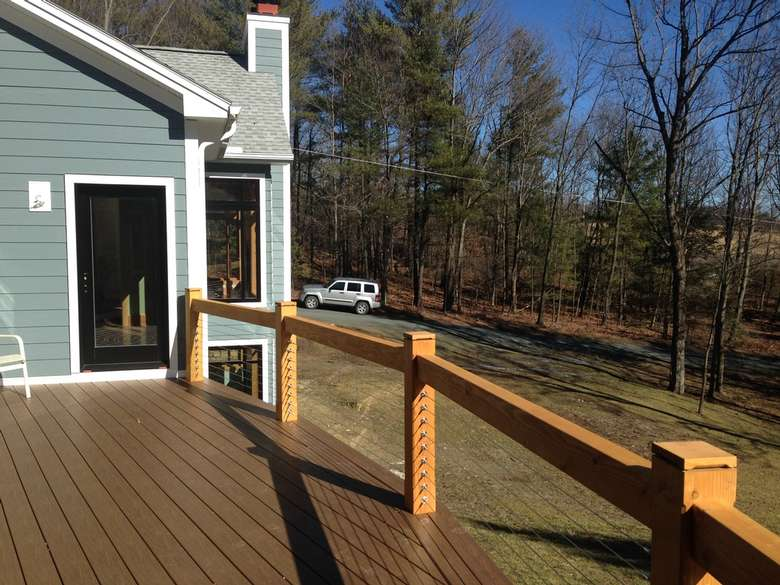 new deck with a modern style railing overlooking a large backyard