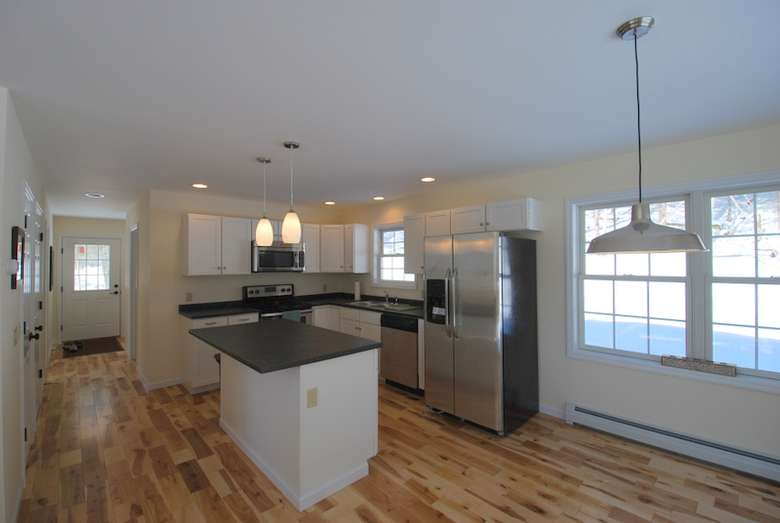 large new kitchen with an island, stainless appliances, and hardwood floors