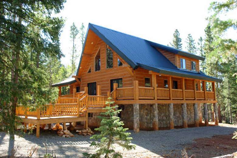 exterior of a new log home with a wrap-around porch and stone foundation