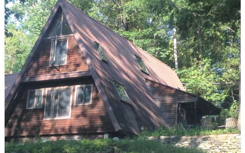 exterior of a large brown a-frame house