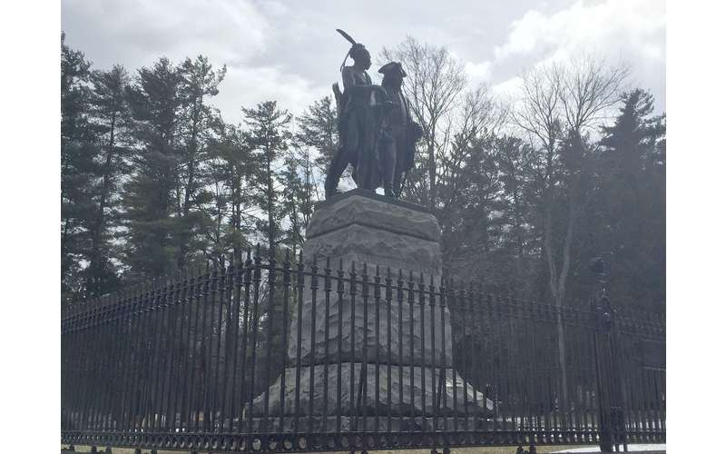 a statue of two men surrounded by a fence