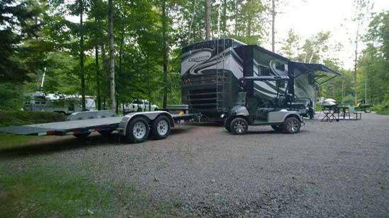 a trailer and golf cart next to a RV