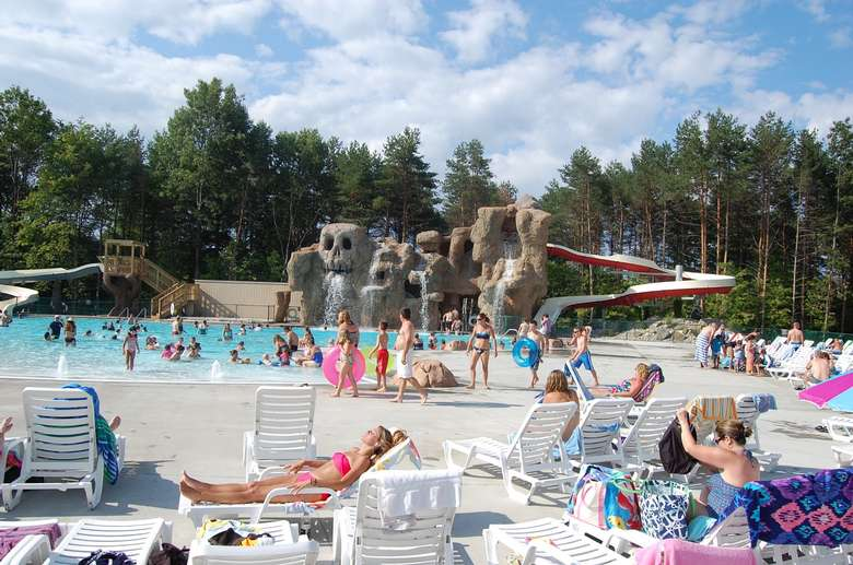 a huge outdoor swimming pool area with people in the water and relaxing in chairs around the edge