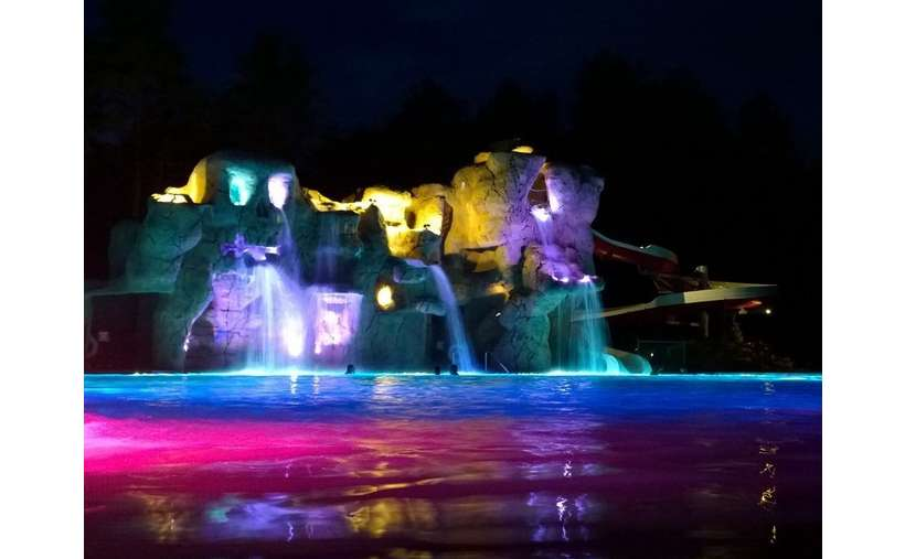 an outdoor swimming pool area with stone attractions in the back, waterfalls, and colored lights at night