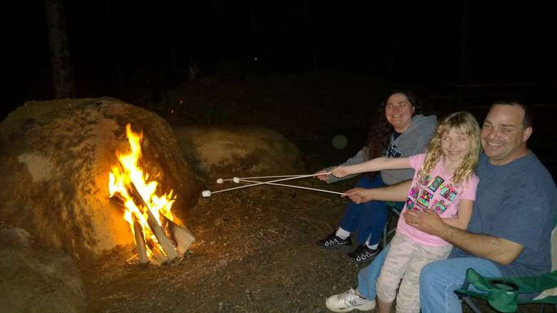 three people sitting by a campfire and roasting marshmallows together