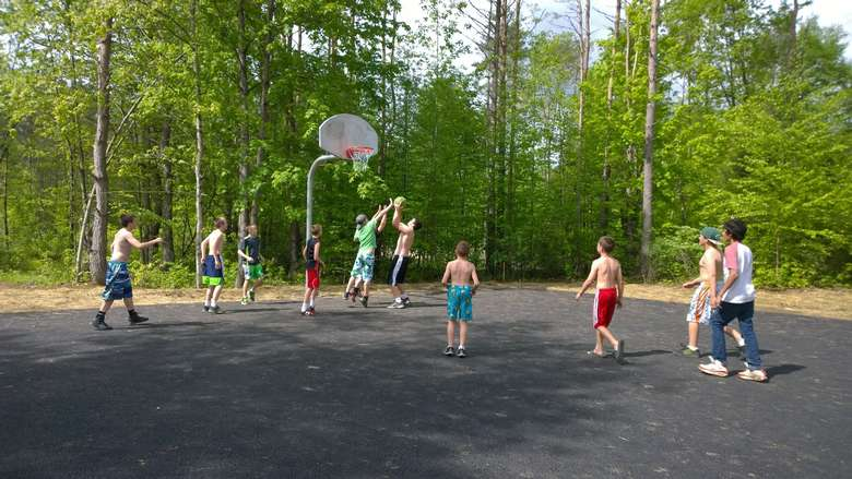 a group of boys playing basketball on an outdoor court area
