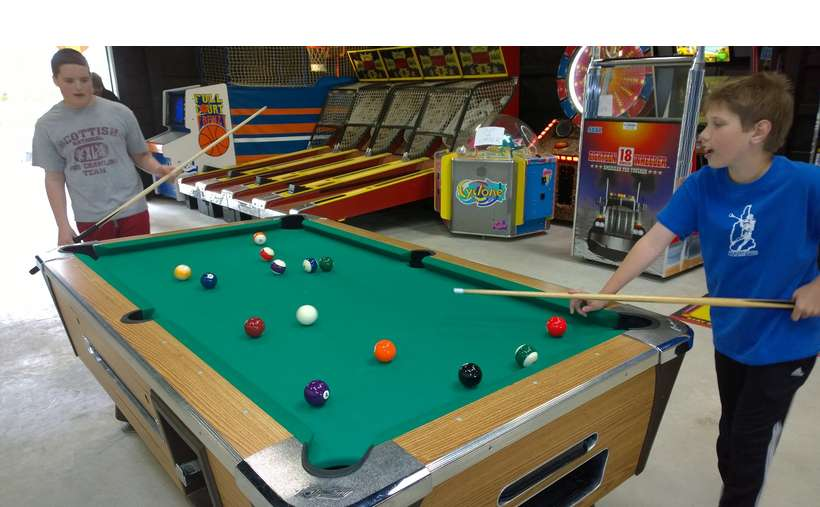 two boys playing pool in a recreation hall