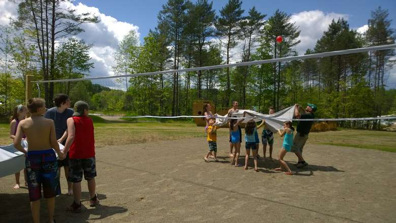 two groups playing games with a ball and blankets at a volleyball court