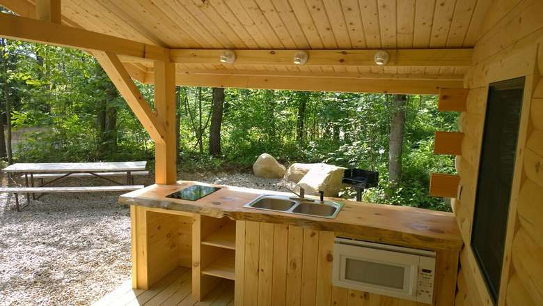 an outdoor kitchen area at a cabin with a sink and a microwave