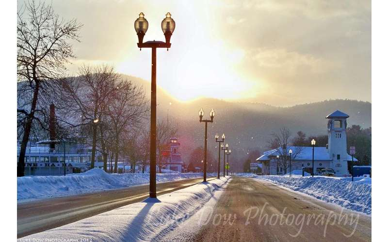 lamp posts along a road during winter, sun is shining in the sky