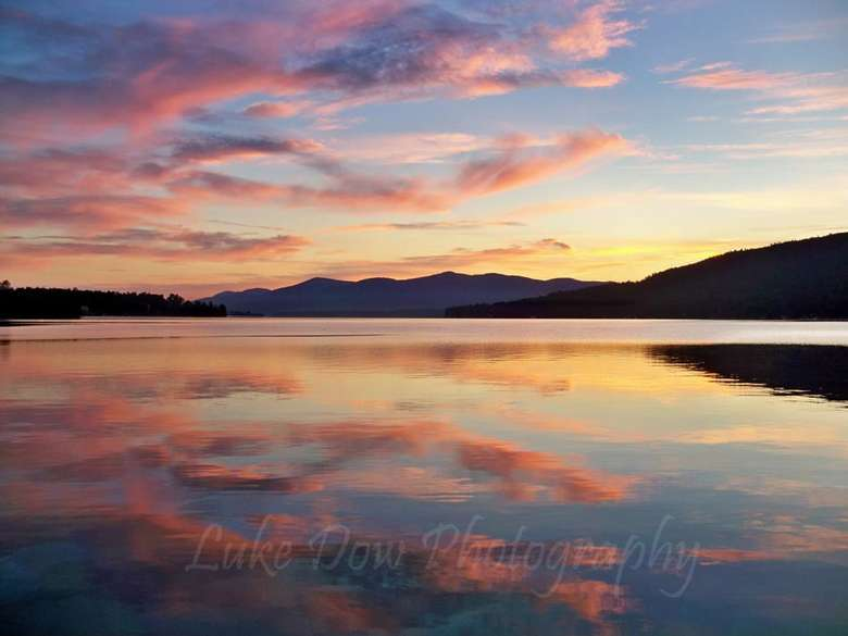 bright and pink colors in the sky during dawn over a lake