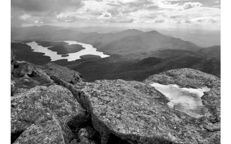 a black and white photograph of a mountain landscape from the summit of a peak