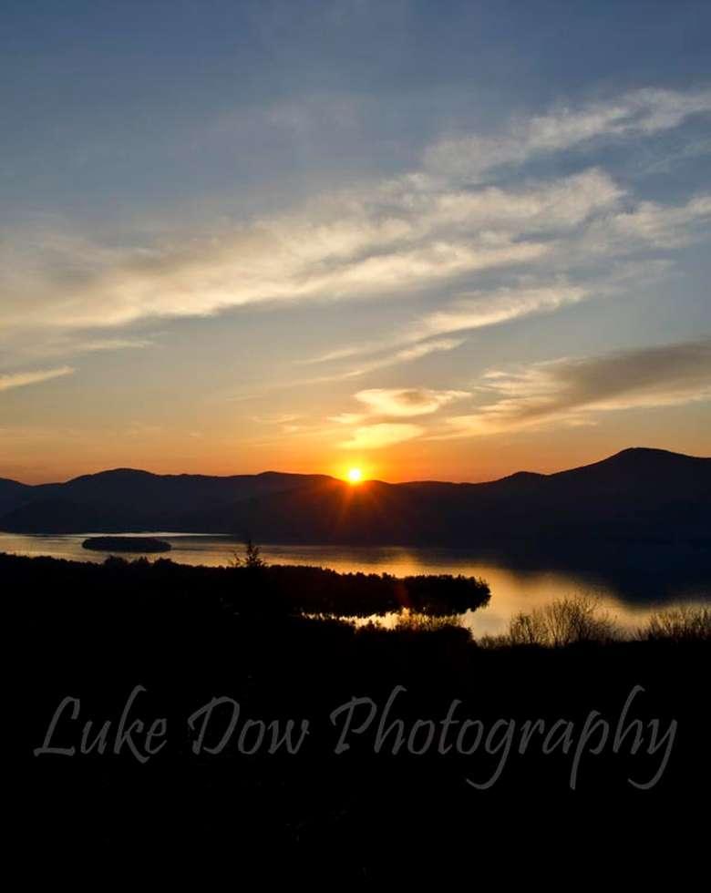 a bright sunrise shining over a lake and mountain
