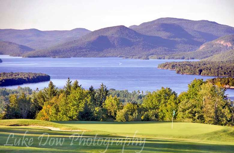 grassy golf course near trees with views of a lake and mountains in the background
