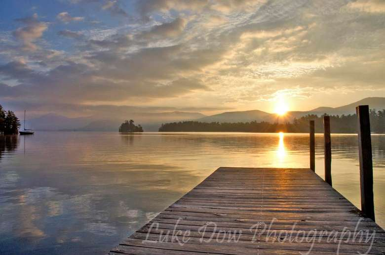 the sun rising over a mountain in the background, a dock is near the shoreline