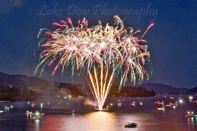 colorful fireworks firing off over a lake