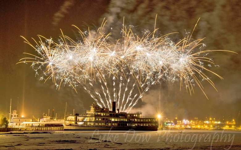 a huge fireworks display over a cruise ship