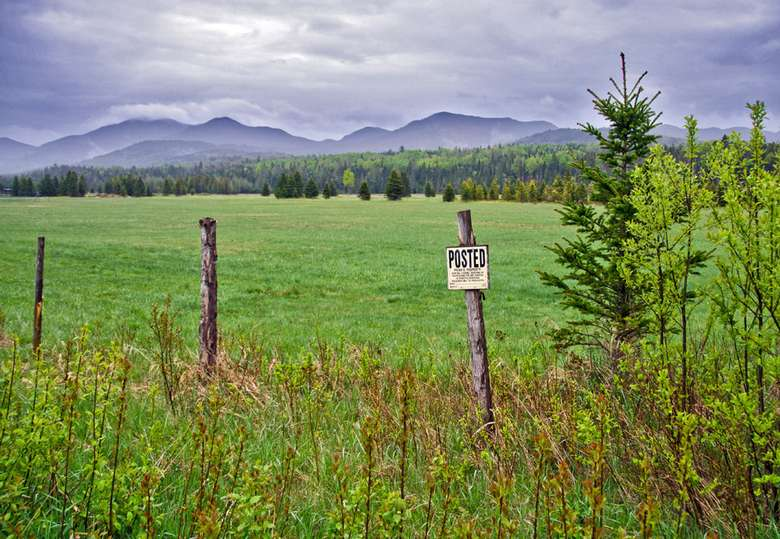a posted sign on a fence post surrounding a farm field