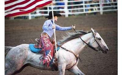 woman riding a horse and holding an american flag