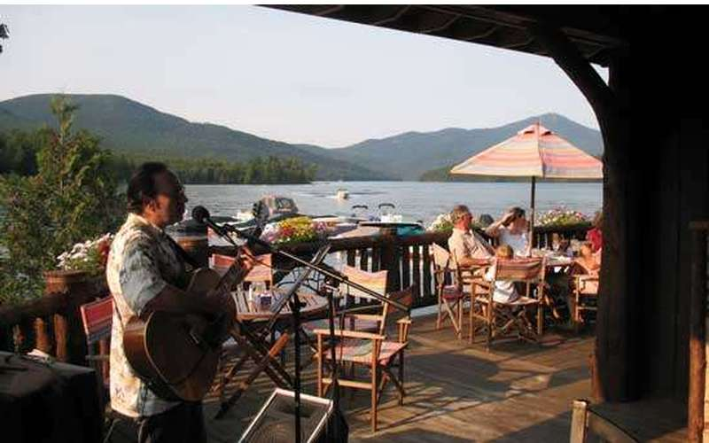 man playing a guitar on wooden patio deck of a waterfront restaurant