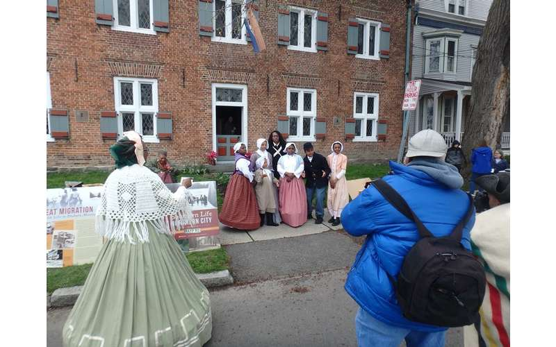 men and women in period costumes in front of the Myers House