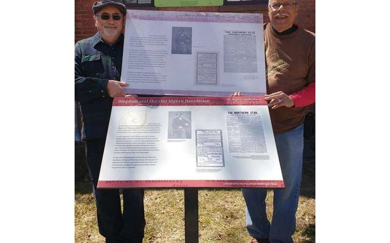two men holding up a new sign for the Myers House