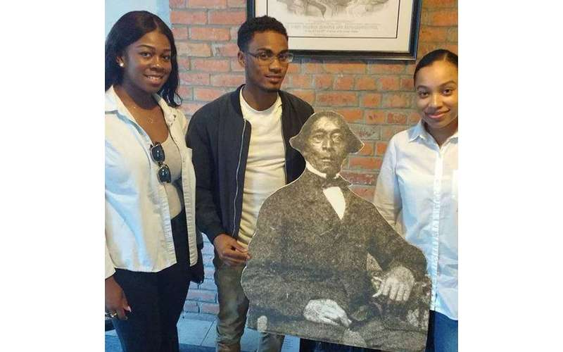 three teenagers standing around a cardboard image of Stephen Myers