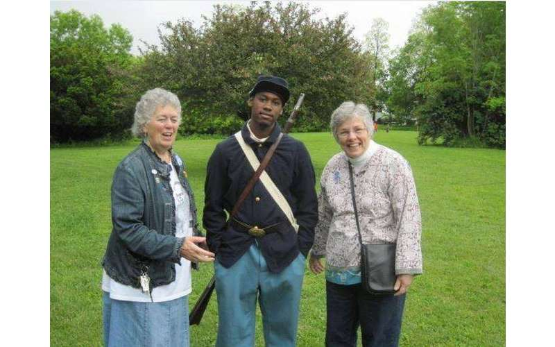 two older ladies standing beside a teenage boy dressed as a Union soldier