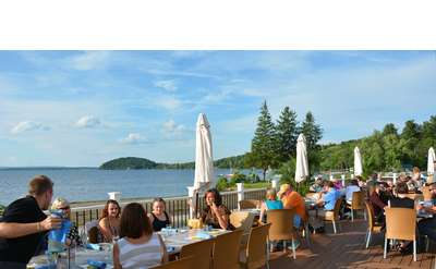 an expansive deck by the lake with people dining