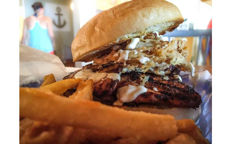 a burger with crispy fried onions