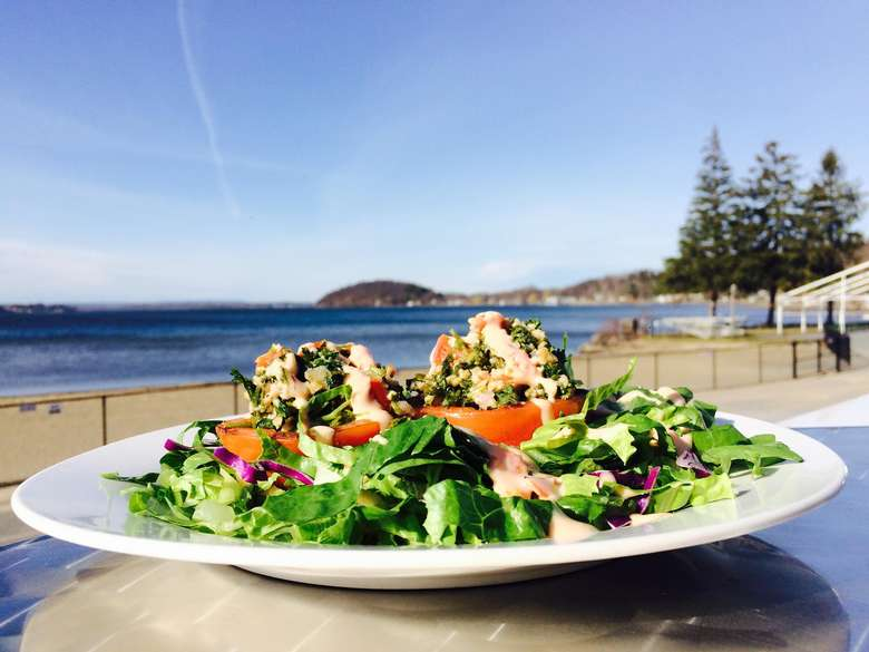 a plate of salad on a table outdoors by the lake