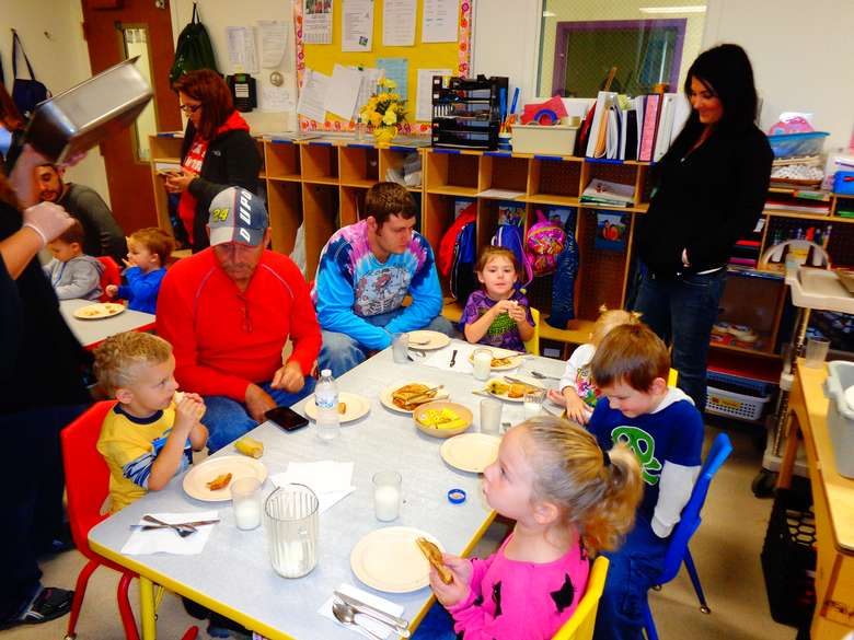 Dads and kids at tables in the head start classroom