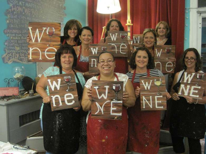 group of women holding up hand-painted wine signs