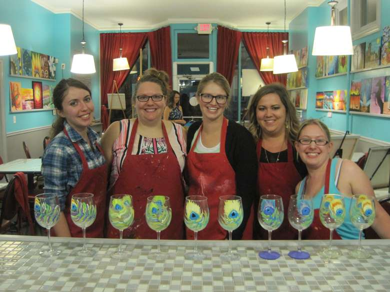 five women standing behind hand-painted wine glasses