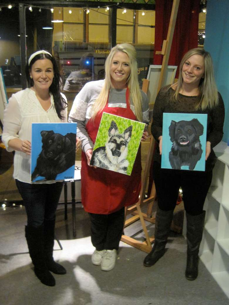 three women holding up paintings of their dogs