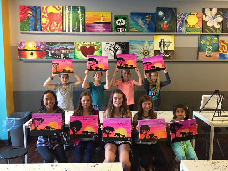 group of kids holding up their paintings
