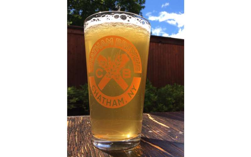 a glass of beer outside with Chatham Brewery logo