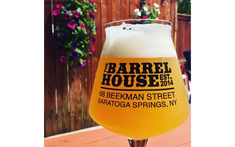 a glass of beer outside with the Barrelhouse logo