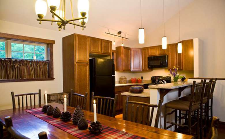 adirondack-style kitchen with tall wooden cabinets and wooden chairs