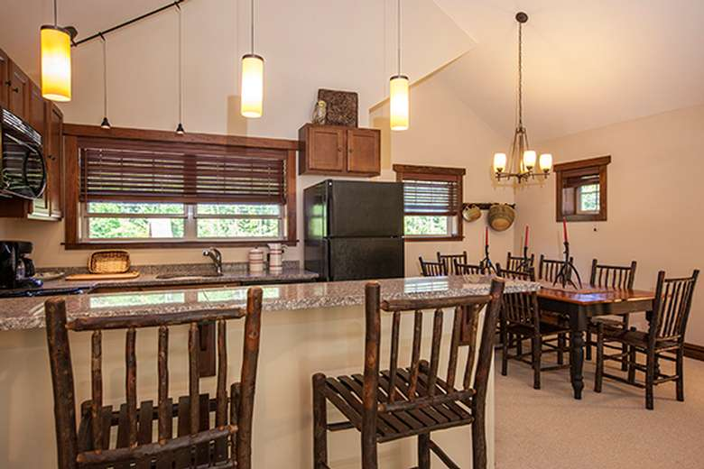 adirondack style kitchen with wooden bar stools a long table with wooden chairs, and wooden cabinets