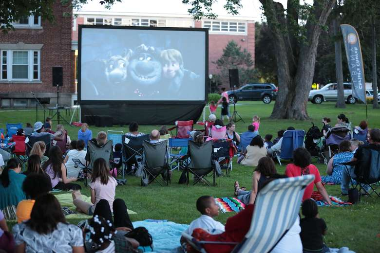 lawn full of people in chairs and on blankets watching a movie projected onto a large screen