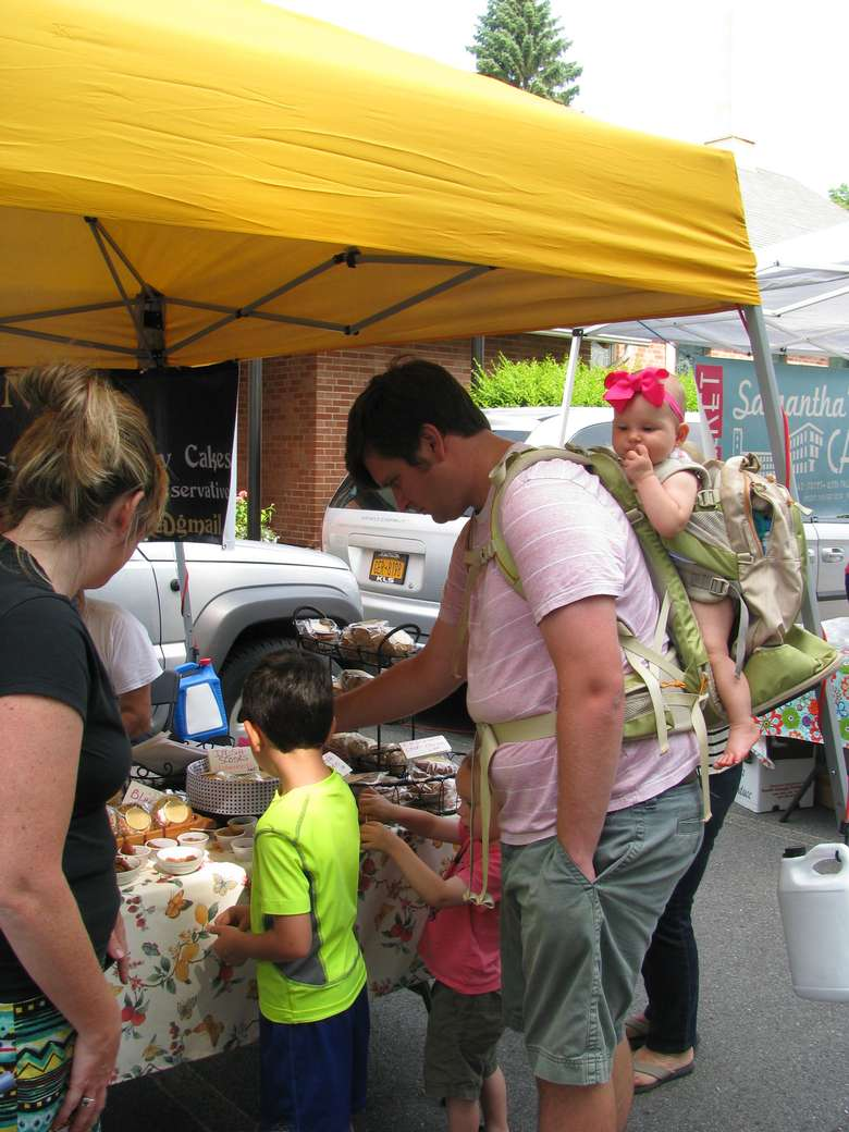 a woman with a baby in a carrier on her back at a vendor booth