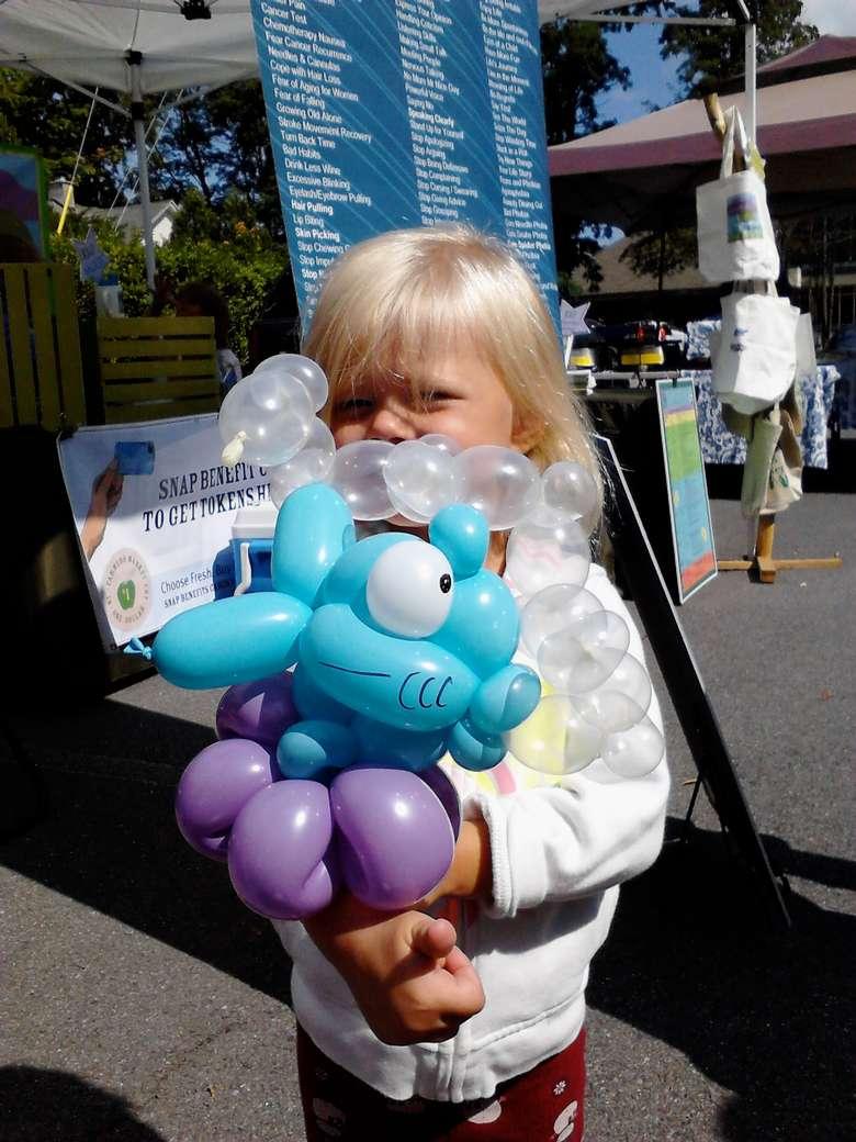 a little girl with a balloon animal