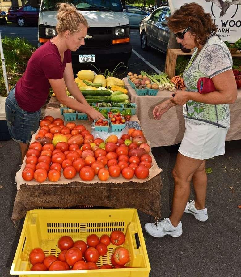 woman looking at tomatoes