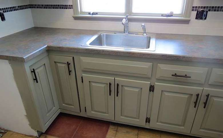 a long kitchen cabinet space with a sink the middle one