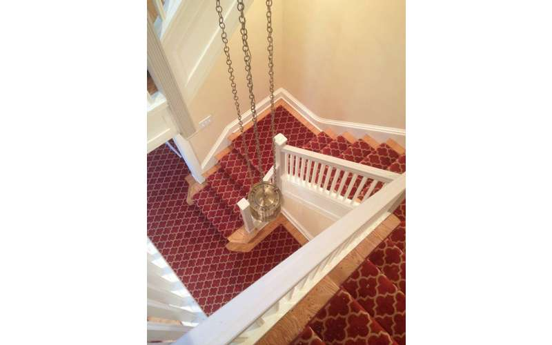 a stairway with multiple corners and red carpeting