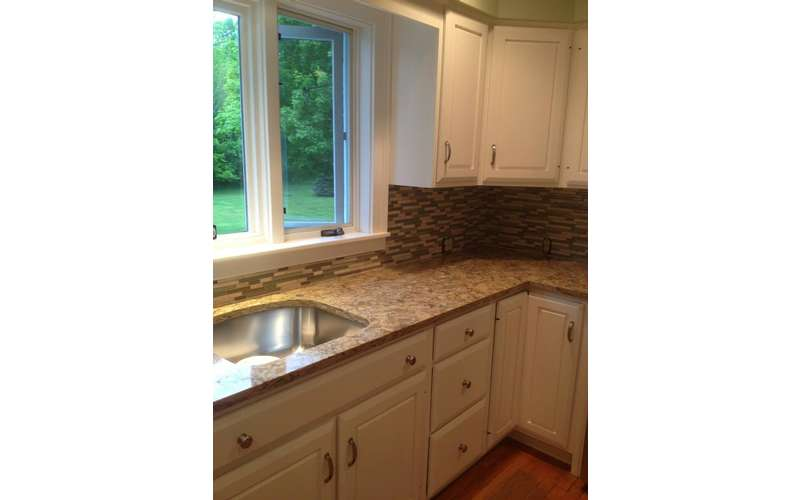 a kitchen with a sink, cabinet countertops, and a window