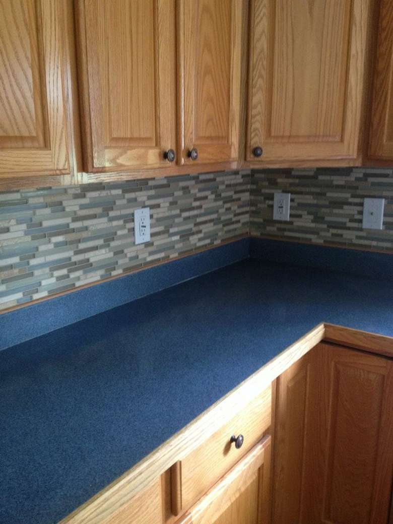 a blue countertop on cabinets and drawers with more cabinets above