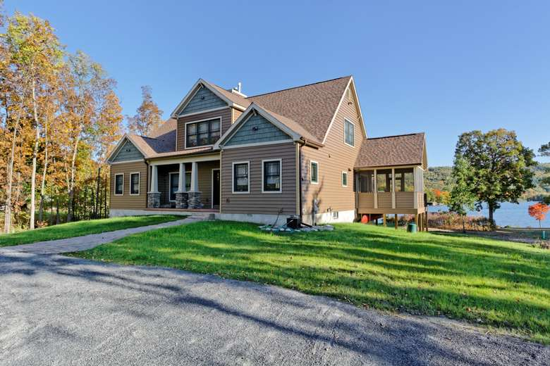a large, tan, modified cape cod style home with a three-season screened in porch on a large grassy lot by a lake